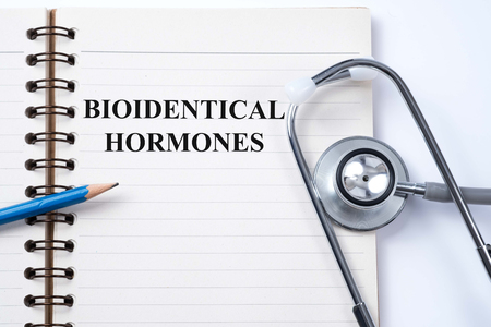 Stethoscope on notebook and pencil with bioidentical hormones words as medical concept