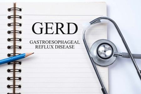 gastroenterology: Stethoscope on notebook and pencil with GERD (Gastroesophageal Reflux Disease) words as medical concept.