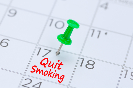Quit Smoking written on  a calendar with a green push pin to remind you and important appointment.