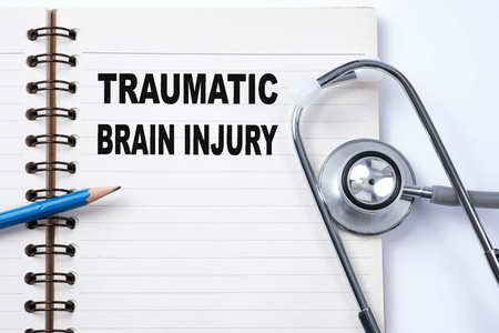 Stethoscope on notebook and pencil with TRAUMATIC BRAIN INJURY words as medical concept. Stock Photo
