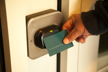Traveler opening hotel room door by plastic keycard. Stock Photo