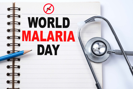 Stethoscope on notebook and pencil with WORLD MALARIA DAY words as medical concept. Stock Photo