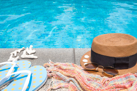 Concept of holiday tropical on summer, Accessories blue slippers, rainbow scarf, straw hat, shell, coral and sunglasses on border of a swimming pool. Stock Photo