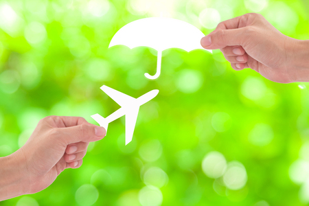 Hand holding a paper airplane and umbrella on green background, Travel Insurance
