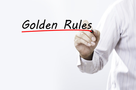 golden section: Businessman hand writing Golden Rules with red marker on transparent wipe board, business concept