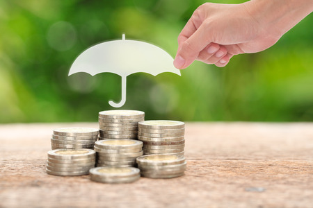 paper umbrella: Woman hand holding a paper umbrella stacks and heaps of coins, nature background. Coverage, insurance or protection concept. Stock Photo