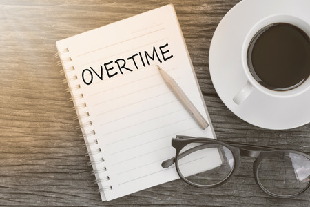 Concept Overtime message on notebook with glasses, pencil and coffee cup on wooden table.