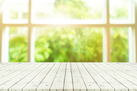 Perspective wooden table on top over blur background view from the coffee shop window, can be used mock up for montage products display or design layout. Archivio Fotografico