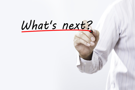 Businessman hand writing What's next with red marker on transparent wipe board, business concept