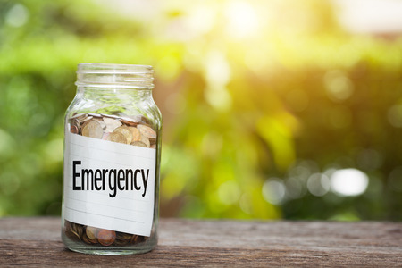 Emergency word with coin in glass jar with Savings and financial investment concept.
