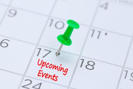Próximos eventos escritos en un calendario con un alfiler verde para recordarte y una cita importante. Foto de archivo