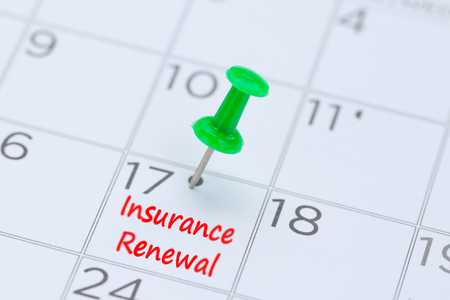 Insurance Renewal written on a calendar with a green push pin to remind you and important appointment.