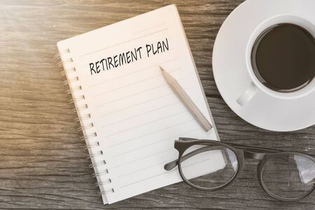 retirement plan concept on notebook with glasses, pencil and coffee cup on wooden table. Stock Photo