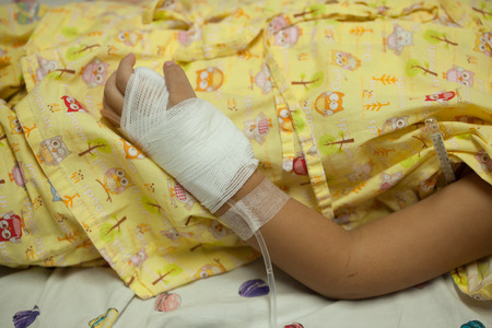 Closeup of hands of a little Boy attaching intravenous tube to patients hand in hospital bed Stock Photo