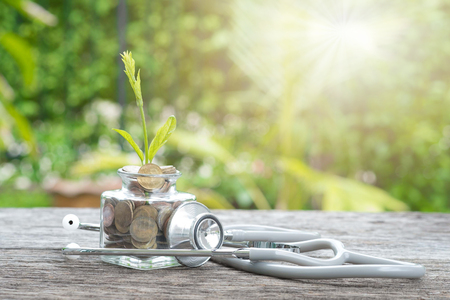 Stethoscope on bottle, coin and plant on wooden background. Concept of financial planning for health care. Stock Photo