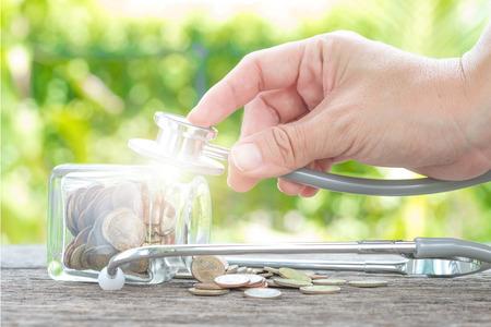 ボトルと木製の背景にコインに聴診器。金融健康チェックやビジネス、財務分析、監査や会計のコストの概念。