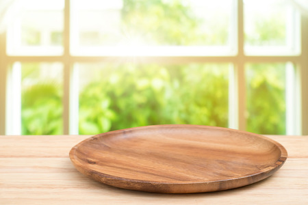counter top: Empty wooden tray on perspective wooden table on top over blur background view from the coffee shop window. Can be used mock up for montage products display or design layout. Stock Photo