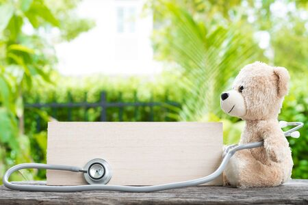 Honey bear with blank banner and Stethoscope on wooden background.