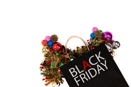 overhead shot of black paper bag with black friday word and christmas decorations on white background