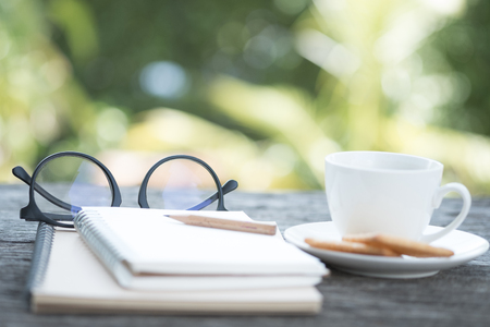 Open empty notebook with pencil, glasses, black coffee and biscuits. Blur picture Stock Photo