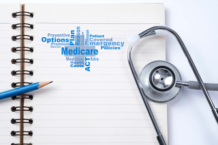 Stethoscope on notebook and pencil with medicare word  as medical concept.