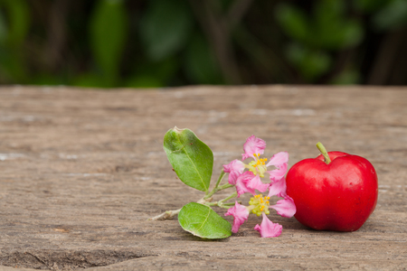 Acerola cherry and flower of thailand on wood. Select focus, Barbados cherry, Malpighia emarginata, high vitamin