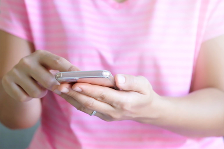 Close up woman hands holding using cell phone for online shopping on sofa in the living room of the house. Stock Photo