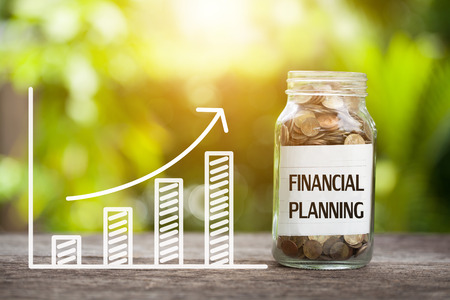 Planowanie finansowe słowo z monetą w szklanym słoju i wykres w górę. Zdjęcie Seryjne