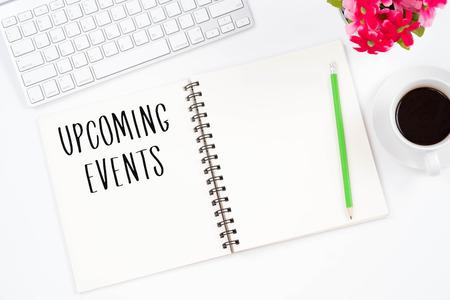 Concepto Próximos eventos mensaje en el cuaderno, teclado, con lápiz y taza de café. Top viwe del lugar de trabajo moderno.
