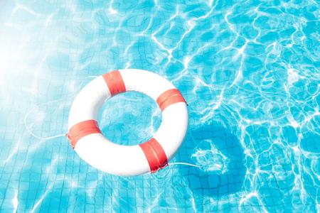 Lifebuoy floating on blue swimming pool.