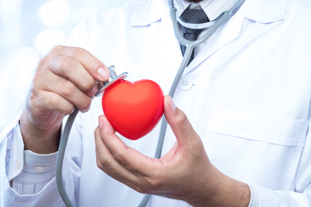 Professional medical doctor holding a stethoscope check up on a red heart ball on blur office in the hospital and bokeh background. Concept of health care. Stock Photo