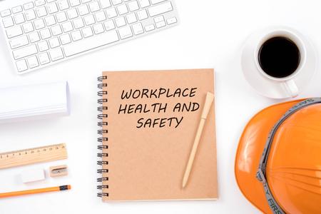 Konzept für Sicherheit und Gesundheitsschutz am Arbeitsplatz. Spitzenviwe des modernen Arbeitsplatzes mit Schutzhelm, Büroartikel, einem Tasse Kaffee und Tastatur auf weißem Hintergrund.