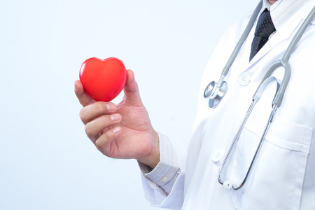 Professional medical doctor holding a red heart ball in the hospital background. Concept of health care.