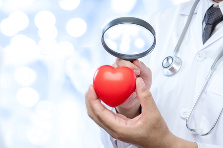 Professional medical doctor holding a magnifying glass check up on a red heart ball on blur office in the hospital and bokeh background. Concept of health care.