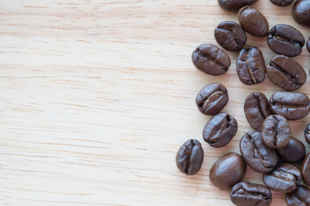 Coffee beans with copy space for text on wood background. Фото со стока