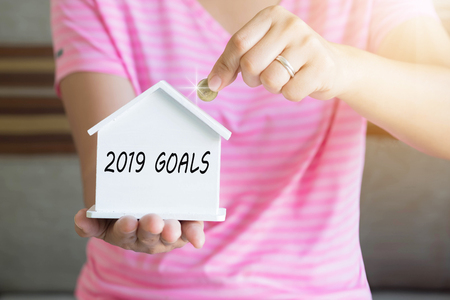 2019 goals with women hand putting money coin in piggy bank, Saving money concept, concept of financial savings to buy a house, Growth, business, money. Stock Photo