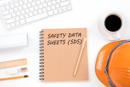Concept SAFETY DATA SHEETS (SDS). Top viwe of modern workplace with safety helmet, office supplies, a cup of coffee and keyboard on white background. Safety & Health. Stockfoto