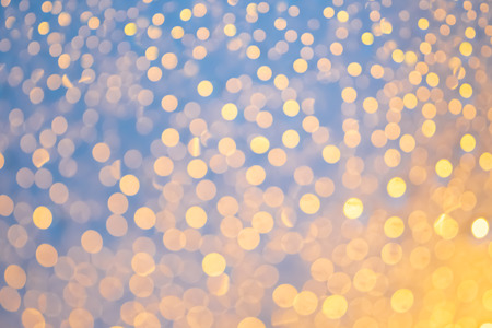 Blur of beautiful water drops on window glass and many bokeh in night light. Water drops on rainy day  for background. Stock Photo