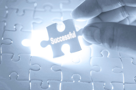 Businessman hand holding a jigsaw puzzle with successful word. Stock Photo
