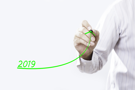 Businessman hand writing growth graph for year 2019