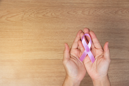 Womens health care concept. Women hands holding pink bow, pink ribbons, on wooden background, Breast Cancer concept. Stock Photo