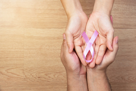 Womens health care concept. Man hands and women hands holding pink bow, pink ribbons, on wooden background, Breast Cancer concept.