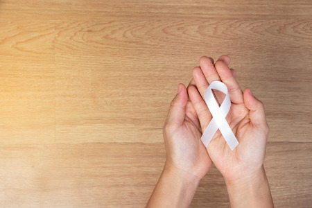 women hands holding white bow, white ribbons on wooden background. Awareness White ribbon for campaign to end violence against women and cancer health care concept Stock Photo