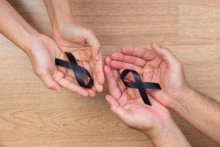 Man hands holding a black ribbon on wooden background Stock Photo