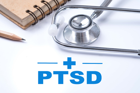 Stethoscope, notebook and pencil with PTSD - post traumatic stress disorder words. Medical concept. War veteran mental health issue. Stock Photo