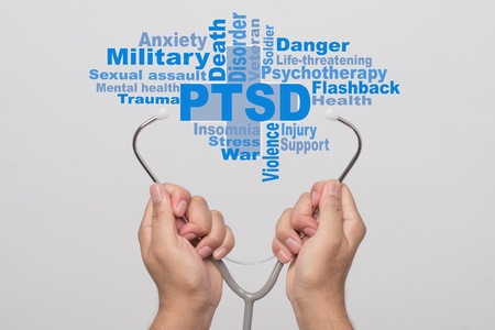 Health Care Concept. Doctor hands holding a stethoscope and PTSD - post traumatic stress disorder words on gray background. War veteran mental health issue. Stock Photo
