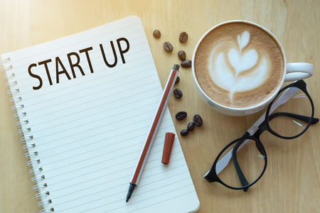Start up concept on notebook with glasses, pencil and coffee cup on wooden table. Business concept.