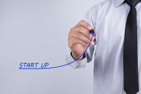 Businessman draw start up word, Training Planning Learning Coaching Business Guide Instructor Leader concept. Stock Photo