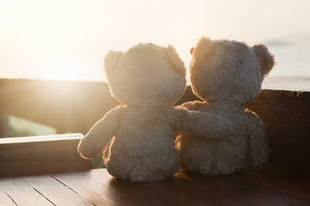 Two teddy bears sitting sea view. Love and relationship concept.  Sunlight in the summer.