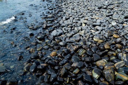 Beautiful wet black stones at Koh Hin Ngam in summer time concept travel, holiday and vacation. Tropical paradise beach nature landscape at Lipe island in Thailand